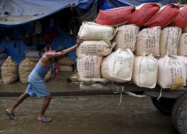 A labourer pushes a handcart loaded with sacks containing tea packets, towards a supply truck at a wholesale market in Kolkata, India, June 26, 2015. For years Indian businesses have lobbied for a nationwide sales tax, hoping to replace a chaotic structure that inflates costs and halts their trucks at state borders for duty payments, and to unify the country into one of the world's largest single markets. (Photo by Rupak De Chowdhuri/Reuters)