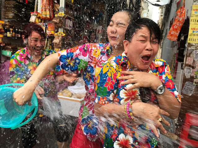 "People spray water in the street ahead of ""Songkran"", the annual Thai New Year water-throwing festival, in Kowloon City, Hong Kong, China, 09 April 2017. The pouring of water is a key element in the festival as it represents purification and the washing away of one's sins and bad luck for the year. The event also includes a ""Miss Songkran"" pageant where contestants are clothed in traditional Thai dress, and a winner is crowned. This year's ""Songkran"" will begin in Thailand on 13 April 2017. (Photo by Alex Hofford/EPA)"