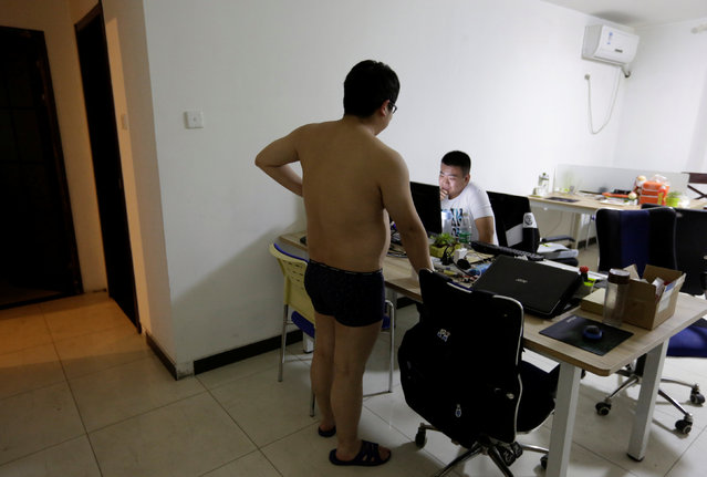 Zhang Huichao, a programmer at N-Wei (Beijing) Technology Company Limited, chats with his colleague Yan Xiaolong before he goes to sleep, in the living room of an apartment which their company rents as office and employees' dormitory, in Beijing, China, April 22, 2016. (Photo by Jason Lee/Reuters)