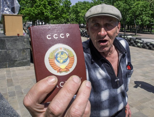 An elderly man brandishes his passport at the camera, with it's cover bearing a former Soviet Union sign, near to barricades at the Ukrainian regional office of the Security Service ahead of the regional referendum in the eastern Ukraine city of Luhansk on Saturday May 10, 2014. The Sunday ballots seek approval for declaring so-called sovereign people's republics in the Donetsk and Luhansk regions. (Photo by Igor Golovniov/AP Photo)