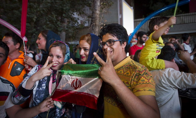 "Iranians gesture as they celebrate in the street following a nuclear deal with major powers, in Tehran July 14, 2015. Iran's president Hassan Rouhani said on Tuesday a nuclear deal with major powers would open a new chapter of cooperation with the outside world after years of sanctions, predicting the ""win-win"" result would gradually eliminate mutual mistrust. (Photo by Reuters/TIMA)"