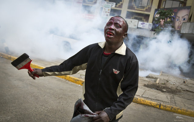 An opposition supporter with a head wound walks past riot police, begging them not to beat him, during a protest in downtown Nairobi, Kenya Monday, May 16, 2016. (Photo by Ben Curtis/AP Photo)