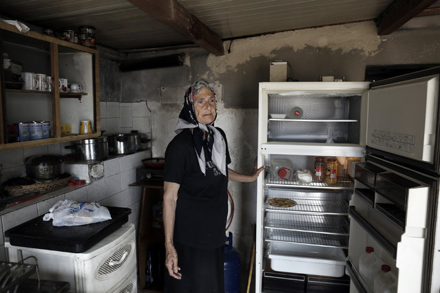 Pensioner Anna Kousoula, 60, displays her empty refrigerator, as she complains because she can not withdraw her pension from the bank due to capital controls, at the kitchen of her home in Perama, near Athens, Greece July 15, 2015. Anna gets 300 euros as a widow's pension and with this small pension helps her son Stratos, who is unemployed for more than four years. (Photo by Yannis Kolesidis/EPA)