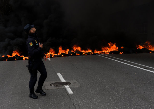 A member of riot police walks in front of a flaming barricade during a May Day rally in Gijon, Spain on May 1, 2017. (Photo by Eloy Alonso/Reuters)
