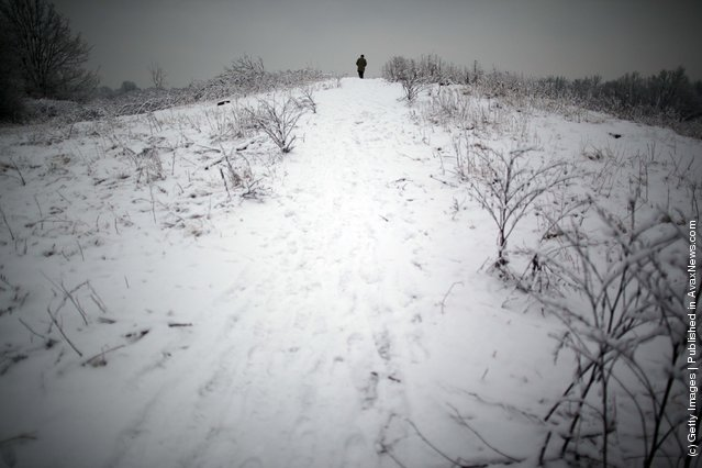 A man walks up a snow covered hill on Wimbledon common on February