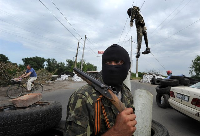 A masked pro-Russian gunman wearing a ribbon of Saint George guards at a check-point near the eastern Ukrainian city of Slavyansk on May 23, 2014. At least five people were killed Friday in fighting near Ukraine's eastern hub of Donetsk two days before a presidential election undermined by an upsurge in attacks by pro-Russian separatists. (Photo by Viktor Drachev/AFP Photo)