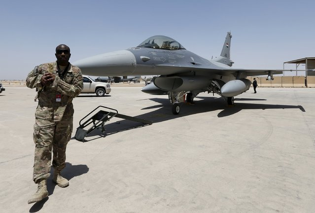 A U.S. Army soldier walks near a F-16 fighter jet during an official ceremony to receive four of these aircrafts from the U.S., at a military base in Balad, Iraq, July 20, 2015. (Photo by Thaier Al-Sudani/Reuters)