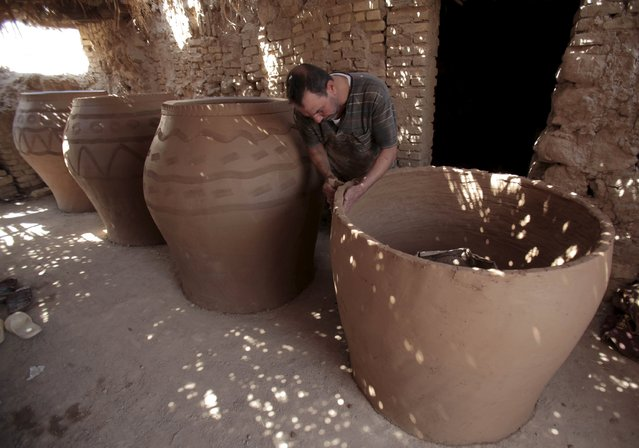 A man makes a mud oven to be used for baking bread at a workshop in Najaf, south of Baghdad, July 23, 2015. (Photo by Alaa Al-Marjani/Reuters)