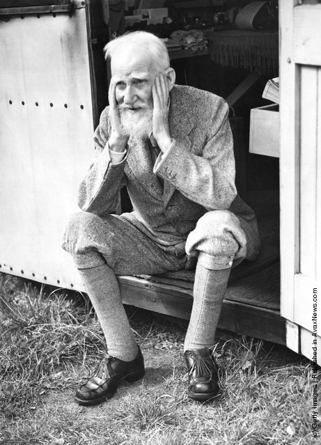 Irish playwright George Bernard Shaw (1856 - 1950) sits in the doorway of the garden shed at his home in Ayot St Lawrence, Hertfordshire, where he does most of his writing, July 1946