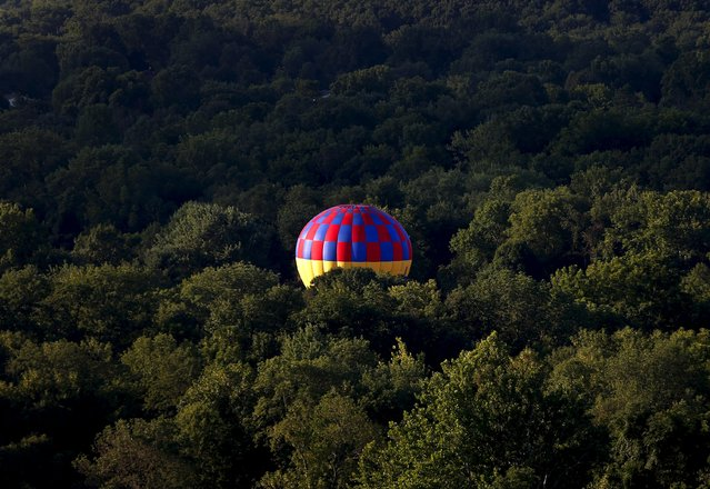 A hot air balloon comes to rest amid trees, as seen from a flying balloon just after sunrise on day one of the 2015 New Jersey Festival of Ballooning in Readington, New Jersey, July 24, 2015. (Photo by Mike Segar/Reuters)