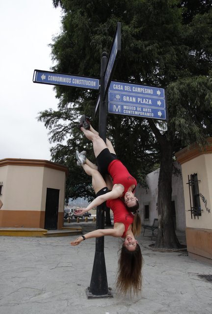 "Women perform a pole dancing routine on a street sign during the national day celebration of ""Urban Pole"" dance in Monterrey June 8, 2014. (Photo by Tomas Bravo/Reuters)"