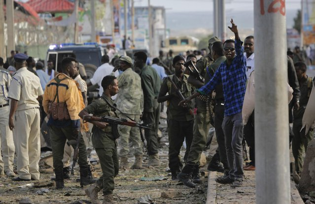 Security forces gather at the scene following a suicide car bomb attack in the capital Mogadishu, Somalia, Sunday, July 26, 2015. A Somali police officer says a suicide car bomber has rammed his car into the protective perimeter outside a well-known hotel in the Somali capital Sunday, killing at least four people. Capt. Mohamed Hussein says the blast has caused an extensive damage on the Jazeera Hotel, which is often frequented by government officials, diplomats and foreigners. (Photo by Farah Abdi Warsameh/AP Photo)
