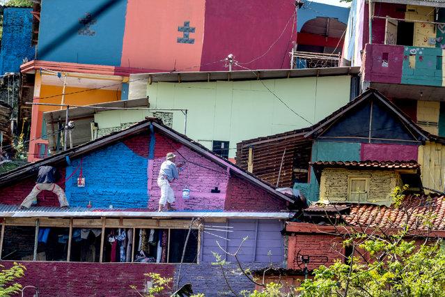 """This picture taken on May 23, 2017 shows workers painting houses at an Indonesian hamlet dubbed """"the rainbow village"""" in Semarang, central Java, that has become an internet sensation and attracting hordes of visitors. The village of about 200 modest homes on a hillside above a river used to be a typical, low-income Indonesian neighbourhood that was filthy and gloomy. But residents of the Wonosari community in Semarang decided an extreme makeover was needed, and received money from the local government and several companies to carry out the project. (Photo by Suryo Wibowo/AFP Photo)"""