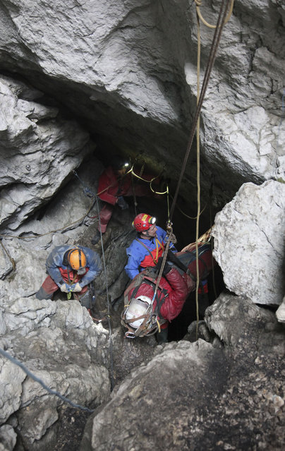 Photo provided by mountain rescue service Bavaria shows rescuers pulling up injured German cave researcher Johann Westhauser out of the country's deepest cavern near Berchtesgaden at the German-Austrian border Thursday, June 19, 2014. The final stretch marked the end of a spectacular rescue operation that lasted nearly a week. Westhauser sustained head injuries in a rock fall June 8 while nearly 1,000 meters (3,280 feet) underground in the Riesending cave system. (Photo by Bergwacht Bayern/AP Photo)