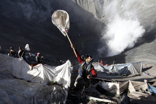 A villager uses a net to catch offerings thrown into the crater of Mount Bromo during Yadnya Kasada festival in Probolinggo, East Java, Indonesia, Saturday, August 1, 2015. (Photo by AP Photo/Trisnadi)