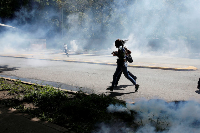 Women run away from tear gas during a protest called by university students against Venezuela's government in Caracas, Venezuela, June 9, 2016. (Photo by Carlos Garcia Rawlins/Reuters)