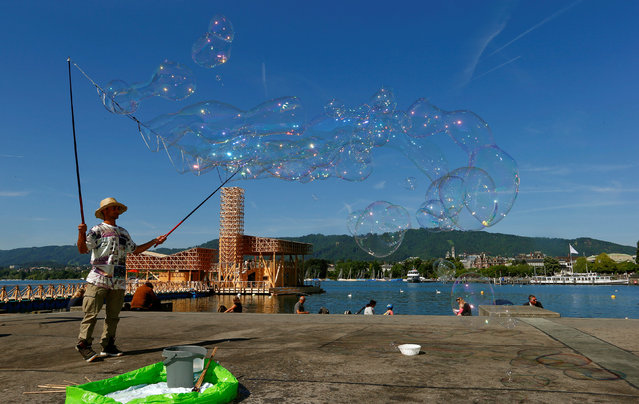 """A man makes giant soap bubbles as he stands in front of the floating """"Pavillon of Reflections"""" of the Manifesta 11 – European Biennial of Contemporary Art on Lake Zurich in Zurich, Switzerland June 10, 2016. (Photo by Arnd Wiegmann/Reuters)"""