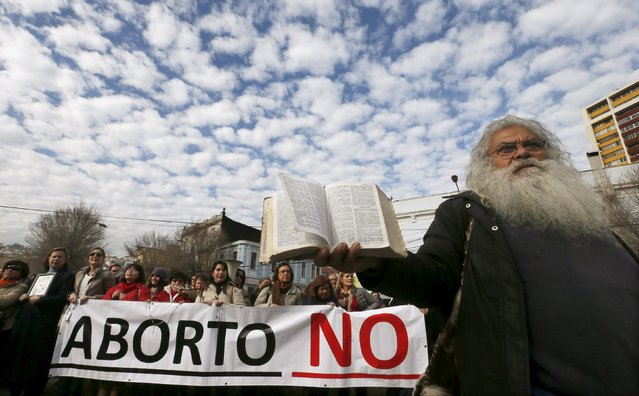 A demonstrator prays with the Bible outside of the congress during a rally against the draft law of the Chilean government which seeks to legalize abortion, in Valparaiso, August 4, 2015. President Michelle Bachelet's push to relax strict abortion laws in socially conservative Chile has created a rift inside her ruling coalition and key elements of the reform are likely to be scratched. (Photo by Rodrigo Garrido/Reuters)