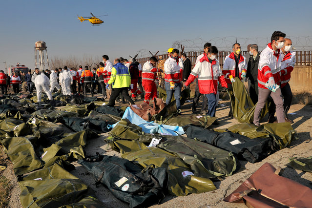 Rescue workers recover bidiesof victims at the scene where a Ukrainian plane crashed in Shahedshahr, southwest of the capital Tehran, Iran, Wednesday, January 8, 2020. The pilot of a Ukranian airliner which crashed in Tehran did not make a call for radio help and was trying to turn back to the airport when the plane plunged from the sky, according to Iranian investigators. Iran is refusing to hand over the black box recorders of the Boeing 737-800, which burst into flames in mid-air before crashing yesterday – killing all 176 people on board. (Photo by Ebrahim Noroozi/AP Photo)