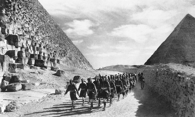 Cameron Highlanders, a Scottish infantry regiment of the British Army, and Indian troops march past the Great Pyramid in the North African Desert, on December 9, 1940