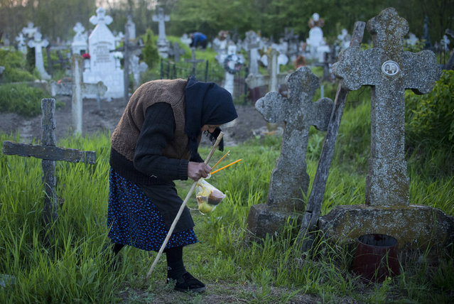 An elderly woman walks to a relative's graves at dawn in Copaciu, southern Romania, Thursday, April 25, 2019. On Maundy Thursday during the holy week of Easter, Orthodox Christians in small southern Romanian villages go to local graveyards before sunrise as part of a centuries-old ritual, light candles and small fires, release incense and leave small bags of food on the ground or offer them with to people. (Photo by Andreea Alexandru/AP Photo)