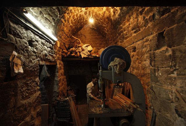 A carpenter works inside his workshop in the old city of Aleppo October 2, 2013. (Photo by Hamid Khatib/Reuters)
