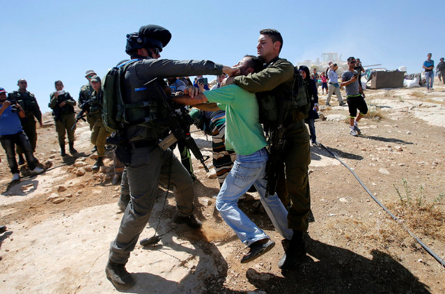 An Israeli border policeman punches a Palestinian man in the face as Israeli troops demolish sheds belonging to Palestinians near the West Bank village of Yatta, south of Hebron June 19, 2016. (Photo by Mussa Qawasma/Reuters)