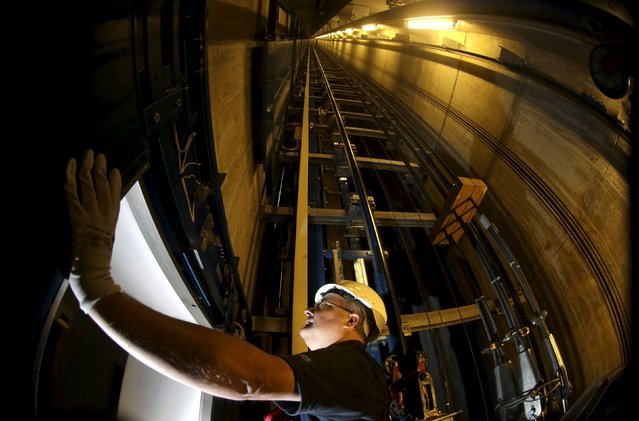 A service engineer of Germany's industrial conglomerate ThyssenKrupp AG inspects the door inside an elevator shaft at an office building in Berlin, Germany in this September 17, 2013 file photo. ThyssenKrupp is expected to report Q3 results this week. (Photo by Tobias Schwarz/Reuters)