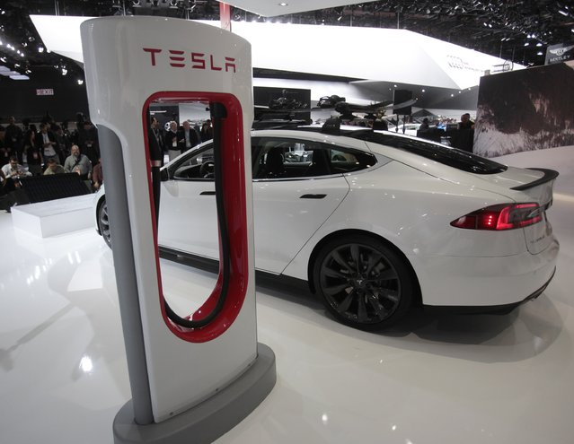 A Tesla S electric car and a charging station are displayed during the press preview day of the North American International Auto Show in Detroit, Michigan, in this file photo taken January 14, 2014. Electric car maker Tesla Motors' operating loss per vehicle has tripled in the past year, to nearly $15,000, and at its current rate of spending, the company would burn through its cash reserves in  less than a year. (Photo by Rebecca Cook/Reuters)