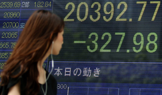 A woman walks past an electronic stock indicator of a securities firm in Tokyo, displaying Tokyo's Nikkei 225 that lost 327.98 points or 1.58 percent to 20,392.77, Wednesday, August 12, 2015. Asian stocks sank as China let its currency fall for a second day following a surprise devaluation that rattled global financial markets. (Photo by Ken Aragaki/AP Photo)