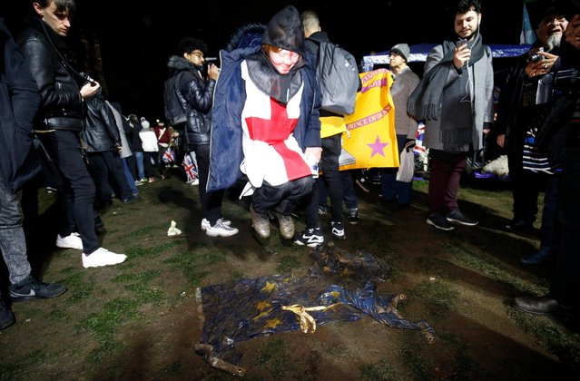A person jumps over the European Union flag lying on the ground and covered with a mud on Brexit day in London, Britain on January 31, 2020. (Photo by Henry Nicholls/Reuters)