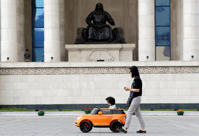A mother follows her daughter playing in a toy car outside the parliament building at Genghis Square in Ulan Bator, Mongolia, June 26, 2016. (Photo by Jason Lee/Reuters)