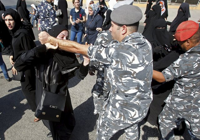 A woman trying to close the road clashes with a Lebanese security officer during a protest against the detention of Sheikh Ahmed al-Assir by Lebanese authorities, in Sidon, south Lebanon August 15, 2015. (Photo by Ali Hashisho/Reuters)