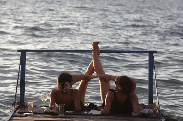 Women enjoy the sunset while lying down on a dock at Ohrid Lake July 27, 2014. The first weekend with warm summer weather has arrived late in Macedonia. (Photo by Ognen Teofilovski/Reuters)