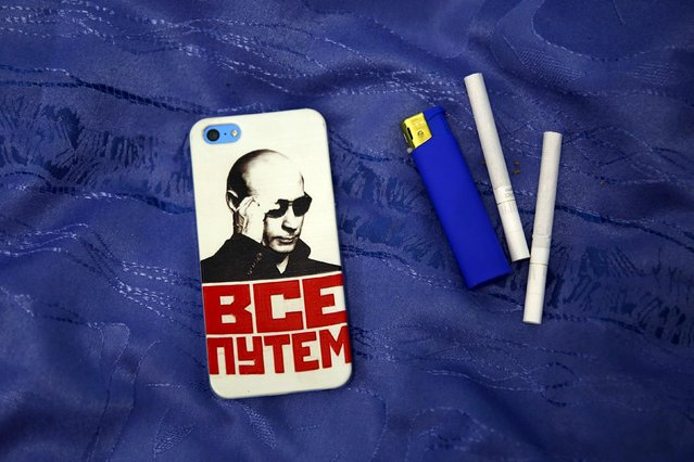 """A mobile phone cover with a picture of Russian President Vladimir Putin and which reads """"Everything is fine"""" is seen in this photo illustration taken in a hotel room in Kazan, Russia, August 5, 2015. (Photo by Stefan Wermuth/Reuters)"""