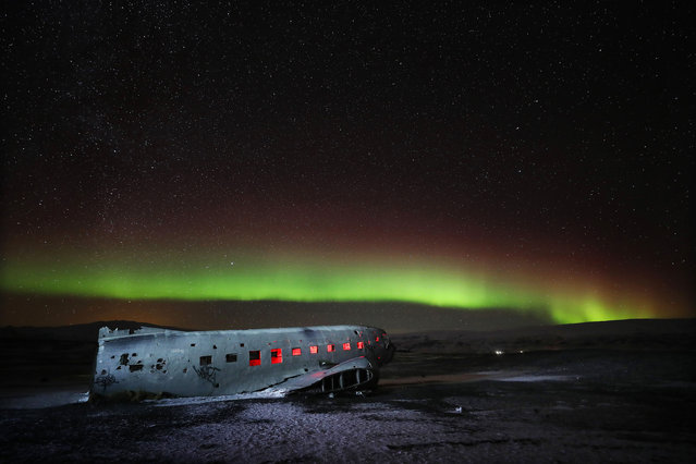Aurora Borealis, or Northern Lights, shine over the plane wreck of a US Navy airplane – a Douglas Super DC-3 – on the Black Beach in Solheimasandur, south Iceland on January 18, 2018. (Photo by Owen Humphreys/PA Images via Getty Images)