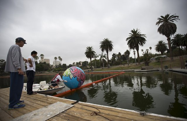 "A volunteer lowers the first inflated sphere into MacArthur Park Lake during the installation of Portraits of Hope's exhibition ""Spheres at MacArthur Park"" in Los Angeles, California August 21, 2015. The installation will feature about 3,000 inflatable hand-painted spheres. (Photo by Mario Anzuoni/Reuters)"