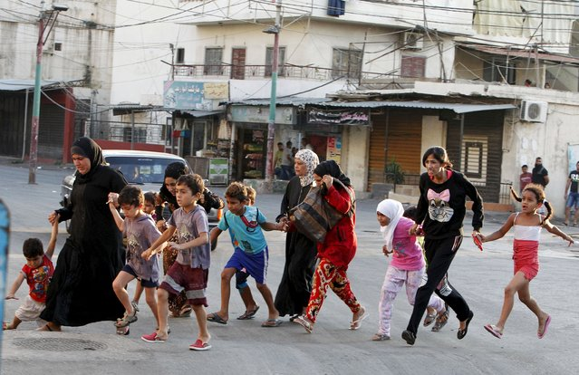 Palestinian residents flee Ain al-Hilweh Palestinian refugee camp, due to clashes in the area, near the port-city of Sidon, southern Lebanon, August 22, 2015. Clashes between Fatah and Jund al-Sham (an Islamist group), in the Ain al-Hilweh Palestinian refugee camp caused the death of 2 and at least 10 wounded, state news agency NNA reported. (Photo by Ali Hashisho/Reuters)