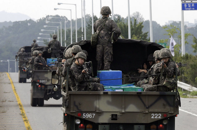 South Korean army soldiers ride on trucks in Paju, south of the demilitarized zone that divides the two Koreas, South Korea, Monday, August 24, 2015. Marathon negotiations by senior officials from the Koreas stretched into a third day on Monday as the rivals tried to pull back from the brink. South Korea's military, meanwhile, said North Korea continued to prepare for a fight, moving unusual numbers of troops, hovercraft and submarines to the border. (Photo by Ahn Young-joon/AP Photo)