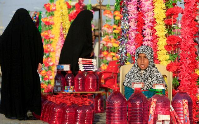 "A girl sells water and flowers at the ""Valley of Peace"" cemetery during the Muslim festival of Eid al-Adha in Najaf, Iraq September 3, 2017. (Photo by Alaa Al-Marjani/Reuters)"