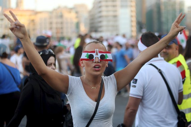 A protester wears sunglasses decorated with Lebanese national flags as she takes part in an anti-government protest at Martyrs' Square in downtown Beirut, Lebanon August 29, 2015. (Photo by Hasan Shaaban/Reuters)