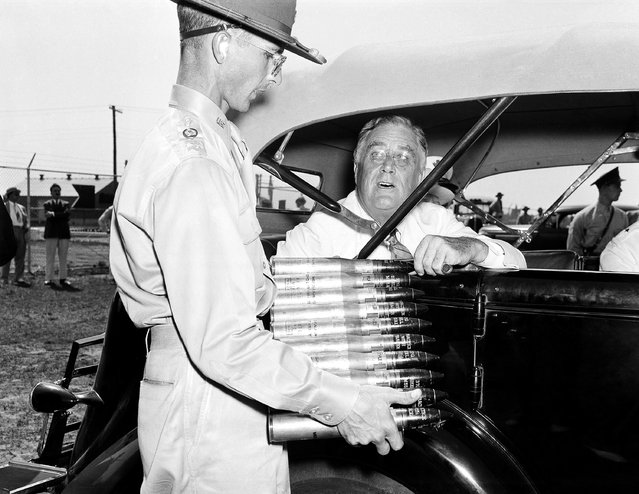 President Franklin D. Roosevelt, on a personal tour to inspect results of the nation's expanded defense program, is looking over a clip of 37 mm. anti-aircraft shells at Langley Field in Hampton, Va., on July 29, 1940, where he stopped on his tour of defense bases. Holding the clip is Lieut. E.H. Waters. (Photo by AP Photo)