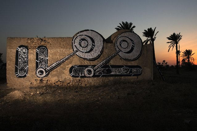 """A mural by Polish artist -CITY decorates an abandoned wall in the surrounding area of the village of Erriadh, on the Tunisian island of Djerba, on August 6, 2014, as part of the artistic project """"Djerbahood"""". (Photo by Joel Saget/AFP Photo)"""