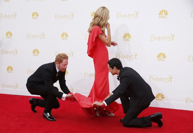 """Jesse Tyler Ferguson from ABC's sitcom """"Modern Family"""" (L) and fashion designer Zac Posen adjust the dress of model Heidi Klum's from Lifetime's reality television series """"Project Runway"""" on the red carpet at the 66th Primetime Emmy Awards in Los Angeles, California August 25, 2014. (Photo by Lucy Nicholson/Reuters)"""