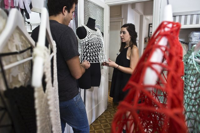 Israeli fashion design student from the Shenkar College of Engineering and Design Danit Peleg (R) speaks to her boyfriend Dan as they look at one of her 3-D printed outfits at her home-based studio in Tel Aviv, Israel August 31, 2015. (Photo by Nir Elias/Reuters)