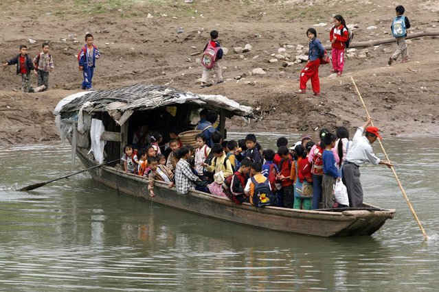 Schoolchildren commute on a ferry from their schools to their homes in Jinhua village, in southwest China's Sichuan province, 17 May 2007. (Photo by Liu Jin/AFP Photo)