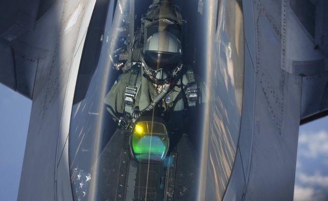 The head-up display of a F-22 Raptor fighter jet reflects the sun light as a pilot of the 95th Fighter Squadron from Tyndall, Florida is seen during refuelling by a KC-135 Stratotanker from the 100th Air Refueling Wing at the Royal Air Force Base in Mildenhall in Britain as they fly over the Baltic Sea towards Spangdahlem airbase, Germany September 4, 2015. (Photo by Wolfgang Rattay/Reuters)