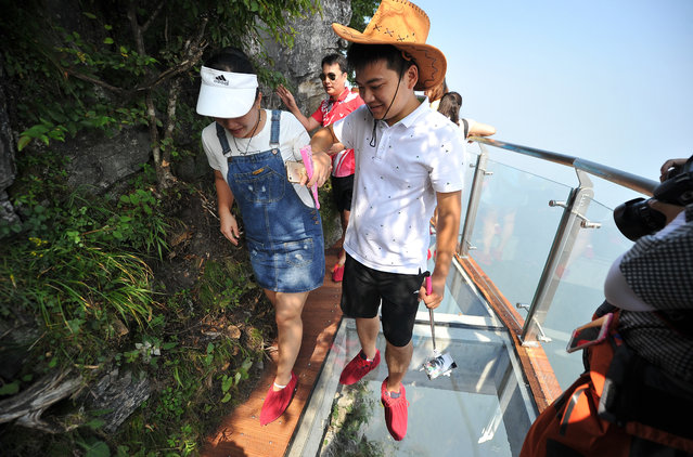 Tourists walk on the 100-meter-long and 1.6-meter-wide glass skywalk clung the cliff of Tianmen Mountain (or Tianmenshan Mountain) in Zhangjiajie National Forest Park on August 1, 2016 in Zhangjiajie, Hunan Province of China. (Photo by VCG/VCG via Getty Images)