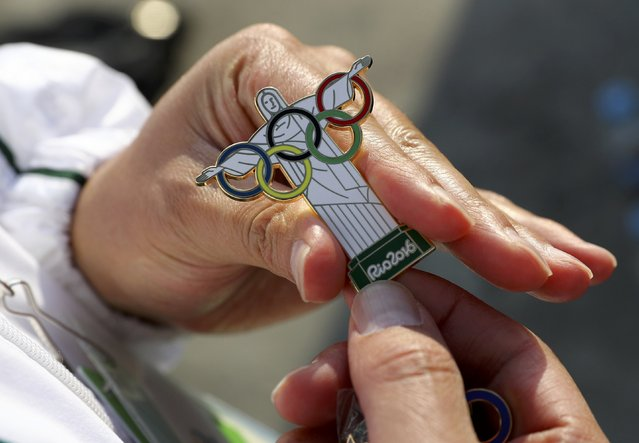 A pin trader shows a Christ the Redeemer Olympic pin ahead of the 2016 Rio Olympics in Rio de Janeiro August 4, 2016. (Photo by Kai Pfaffenbach/Reuters)