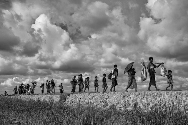 """Rohingya refugees carry their belongings as they walk  on the Bangladesh side of the Naf River after fleeing Myanmar, on October 2, 2017 in Cox's Bazar, Bangladesh. More than half a million Rohingya refugees have flooded into Bangladesh to flee an offensive by Myanmar's military that the United Nations has called """"a textbook example of ethnic cleansing"""". The refugee population is expected to swell further, with thousands more Rohingya Muslims said to be making the perilous journey on foot toward the border, or paying smugglers to take them across by water in wooden boats. Hundreds are known to have died trying to escape, and survivors arrive with horrifying accounts of villages burned, women raped, and scores killed in the 'clearance operations' by Myanmar's army and Buddhist mobs that were sparked by militant attacks on security posts in Rakhine state on August 25, 2017.  What the Rohingya refugees flee to is a different kind of suffering in sprawling makeshift camps rife with fears of malnutrition, cholera, and other diseases.  Aid organizations are struggling to keep pace with the scale of need and the staggering number of them – an estimated 60 percent – who are children arriving alone. Bangladesh, whose acceptance of the refugees has been praised by humanitarian officials for saving lives, has urged the creation of an internationally-recognized 'safe zone' where refugees can return, though Rohingya Muslims have long been persecuted in predominantly Buddhist Myanmar. World leaders are still debating how to confront the country and its de facto leader, Aung San Suu Kyi, a Nobel Peace Prize laureate who championed democracy, but now appears unable or unwilling to stop the army's brutal crackdown. (Photo by Kevin Frayer/Getty Images)"""